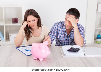 Woman Looking At Piggybank Raised By Young Man
