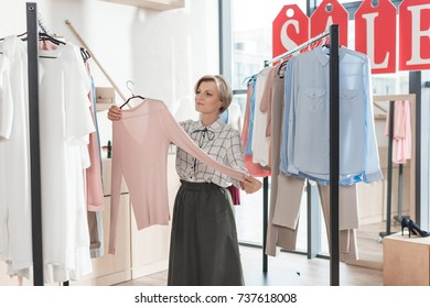 Woman looking at pink shirt in store between racks