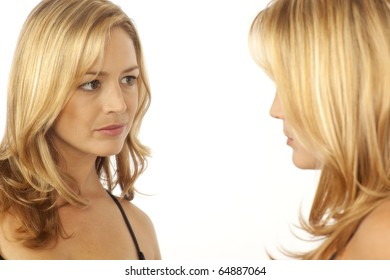 Woman looking at reflection in mirror