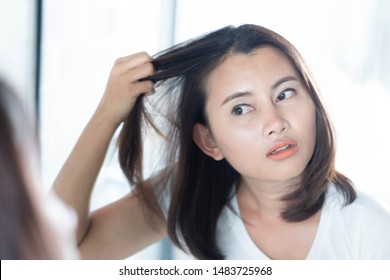 Woman looking reflection in the mirror serious hair loss problem for health care shampoo and beauty product concept