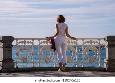 Woman looking at the sea from a balcony