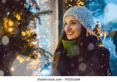 Woman looking in shop window on Christmas shopping gifts