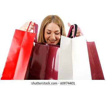 Woman looking in shopping bags smiling,isolated on white