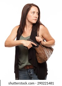 Woman looking to the side and carrying a Concealed Gun in her Purse | Attractive female shooter holding weapon against white background.