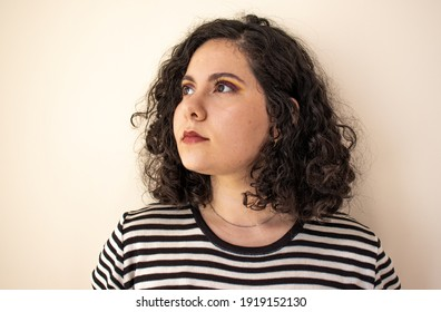 Woman looking to the side in front of a white wall. Curly hair woman with stylish makeup on. Stylish girl with fashion makeup and clothes. Fashionable woman with curly hair.