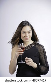 Woman looking to the side has her blowing.She has a glass of wine and a smile upon her face. She is of mixed ethnicity.