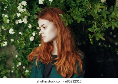 Woman looking sideways against the background of greenery