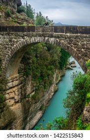 Woman looking at the sky on the ancient bridge. Koprulu Canyon in Manavgat, Antalya, Turkey. Amazing river landscape. Travel, tourism and holiday concept