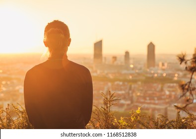 Woman looking at the skyline of the French city of Lyon during a tranquil sunrise.