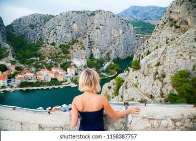 woman looking at the small town Omis, Makarska, Croatia
