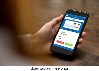 Woman looking at smartphone screen while transferring money online via electronic internet banking application - financial technology or fintech concept