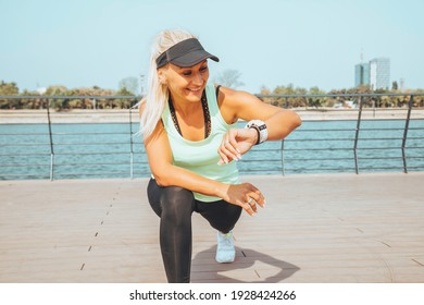 Woman looking at smartwatch heart rate monitor. Healthy lifestyle concept.