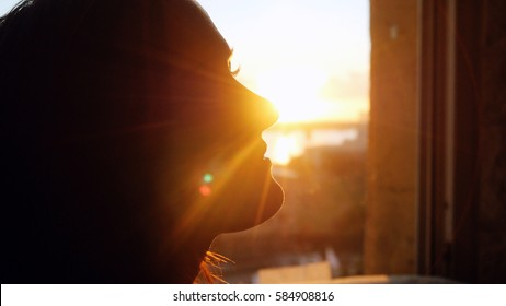 Woman looking standing near the window with view on sunset in city with lense flare effects