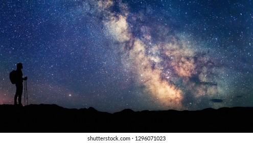 Woman looking at the stars and Milky way. Scenery Landscape with night starry sky and silhouette of standing happy woman. Milky way Galaxy with traveler. Universe.