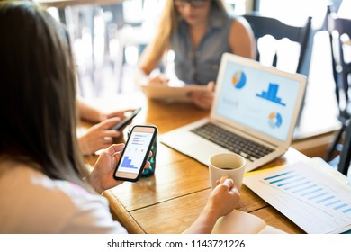 Woman looking at statistical chart on her phone with coworkers working at the table in restaurant