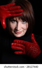 Woman looking straight from dark. In front of her red gloves on her hands. Vertical
