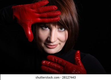 Woman looking straight from dark. In front of her red gloves on her hands. Horizontal