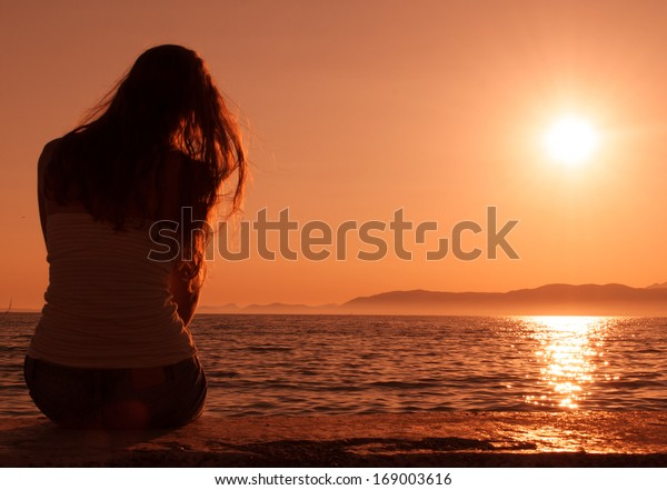 woman looking at the sunset on the beach