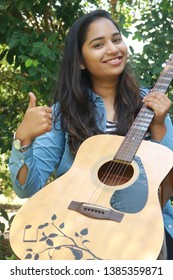 woman looking supersized and happy with a guitar