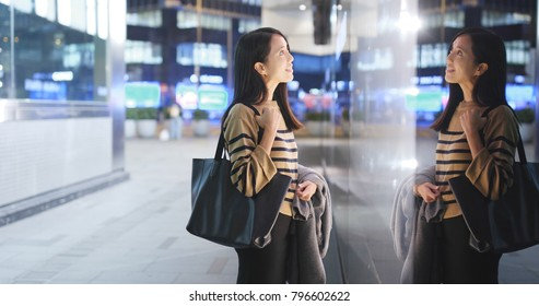 Woman looking though the window and choosing products inside, window shopping concept