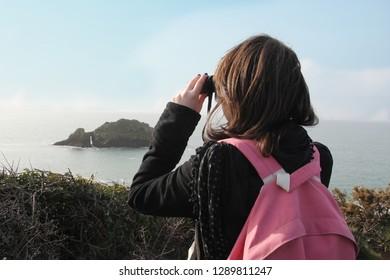 woman looking through binoculars at the atlantic ocean at the Crozon peninsula in France.