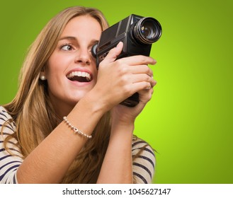 Woman Looking Through A Camera against a green background