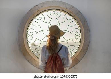 Woman looking through the decorative window in Lisbon Alfama, Portugal