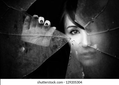 Woman looking through dirty broken glass