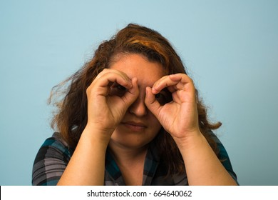 Woman looking through hands, making binoculars