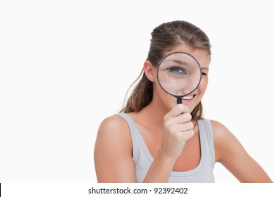 Woman looking through a magnifying glass against a white background