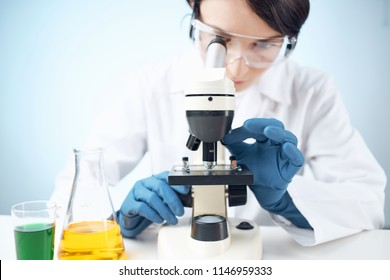 A woman looking through a microscope experiences chemistry.