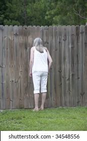 Woman looking through a peephole in a fence to spy on her neighbors!