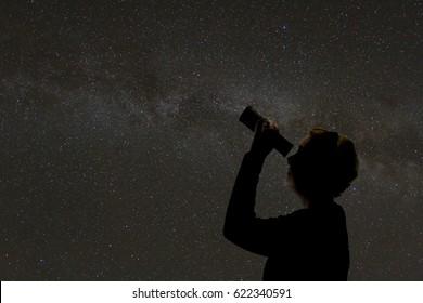 Woman looking through telescope at night sky.