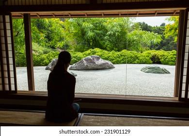 Woman looking through a window at a Japanese Zen Rock Garden.