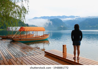 Woman looking at traditional tourist boats (pletna) at pier with reflex on the water. Beautiful scene, mountains with fog. Concept for early retirement, slow down pace of life.