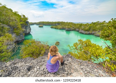 Woman looking at tropical paradise pristine coast line rainforest blue lake at Bair Island. Indonesia Moluccas archipelago, Kei Islands, Banda Sea. Top travel destination, best diving snorkeling.