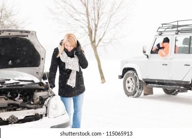Woman looking under broken car hood snow trouble man assistance