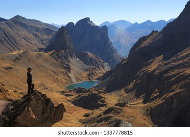 Woman looking at a valley and mountains on a clear, autumn day.