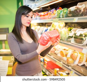 Woman looking at a vegetable in a grocery store