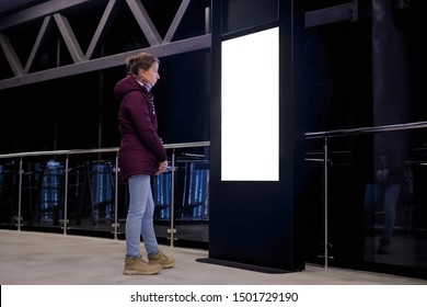 Woman looking at vertical blank interactive white display kiosk at exhibition or museum with futuristic sci-fi interior. Mock up, copyspace, template, isolated, white screen, technology concept