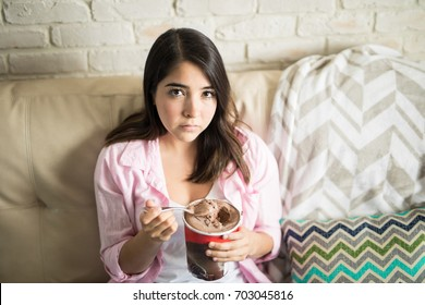 Woman looking very sad after breaking up with her boyfriend and trying to feel better by eating chocolate ice cream
