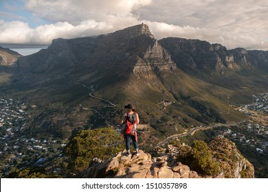 A woman is looking at the view of Table Mountain from a lion's head in Cape Town.