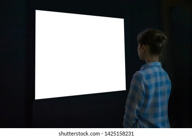 Woman looking at white blank large interactive wall display in dark room of modern technology exhibition. Evening time, low light. Mock up, template, copyspace, education and technology concept