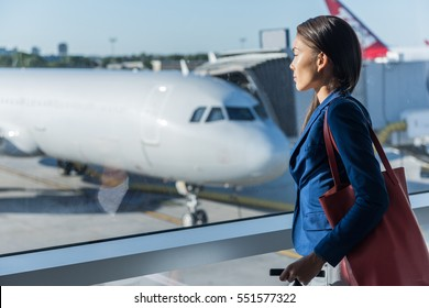 Woman looking at window in airport. Asian tourist relaxing looking at airplanes while waiting at boarding gate before departure. Travel lifestyle.