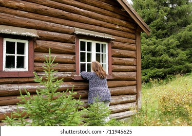 Woman looking in the window of an old cottage