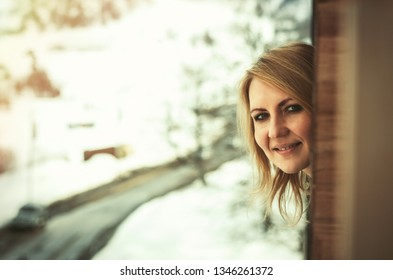 Woman looking from the window. Winter time
