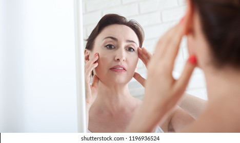 Woman looking at wrinkles in mirror. Plastic surgery and collagen injections. Makeup. Macro face. Selective focus on the face. Realistic images with their own imperfections.