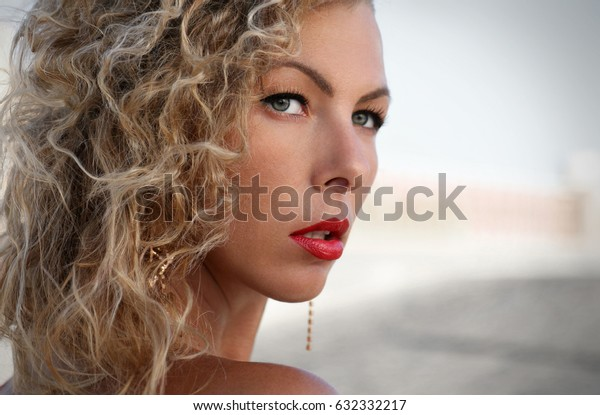 Woman looking at you, woman face portrait with curly blond hair, deep eyes and red lips, fashion beauty photo of the professional model