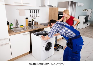 Woman Looking At Young Male Worker With Toolbox Repairing Washing Machine In Kitchen Room