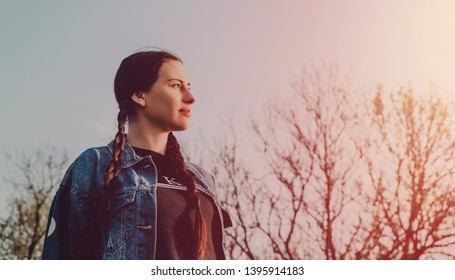 The woman looks ahead into the distance. Concept of reflection, use of the day and the moment.